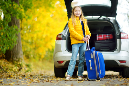 Adorable girl with a suitcase ready to go on vacations with her parents. Child looking forward for a road trip or travel. Autumn break at school. Traveling by car with kids.