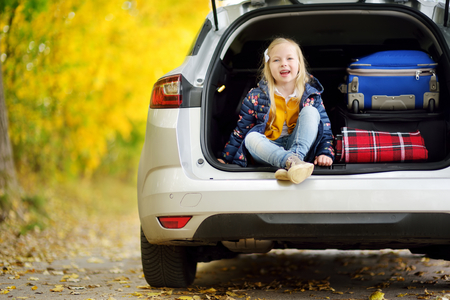 Adorable girl sitting ain a car trunk ready to go on vacations with her parents. Child looking forward for a road trip or travel. Autumn break at school. Traveling by car with kids.