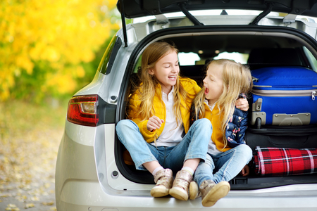 Two adorable girls sitting in a car trunk before going on vacations with their parents. Two kids looking forward for a road trip or travel. Autumn break at school. Family travel by car. 스톡 콘텐츠