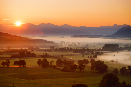 Breathtaking morning lansdcape of small bavarian village covered in fog. Scenic view of Bavarian Alps at sunrise with majestic mountains in the background, Anger, Germany.
