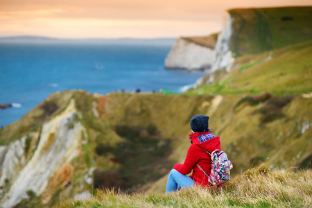 Tourist enjoying view of Man OWar Cove on the Dorset coast in southern England, between the headlands of Durdle Door to the west and Man O War Head to the east, Dorset, England.