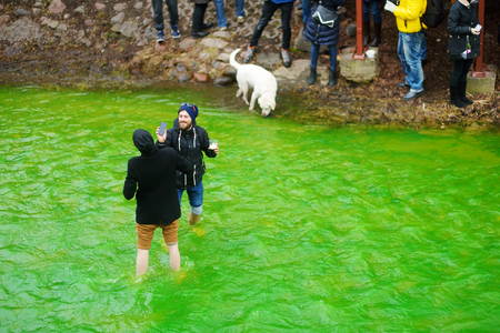 VILNIUS, LITHUANIA - MARCH 18, 2017: Hundreds of people enjoying festivities and celebrating St. Patricks day in Vilnius. Vilnele river was dyed green to mark the patron saint of Irelands day.