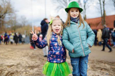 Twee schattige kleine meisjes dragen groene hoeden en accessoires vieren St. Patrick's day in Vilnius. Kinderen plezier hebben op traditionele Ierse festival. Stockfoto - 93307237
