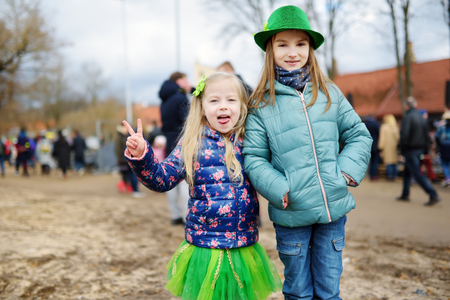Two cute little girls wearing green hats and accessories celebrating St. Patricks day in Vilnius. Children having fun at traditional irish festival. Banco de Imagens