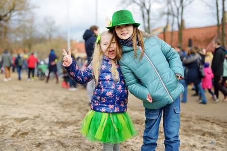 Two cute little girls wearing green hats and accessories celebrating St. Patricks day in Vilnius. Children having fun at traditional irish festival. Stock Photo