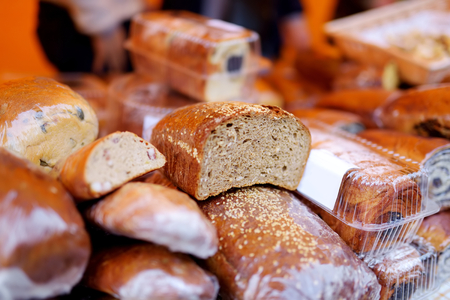 Loaves of organic bread for sale at outdoor farmers market in Vilnius. Traditional spring fair in capital of Lithuania.