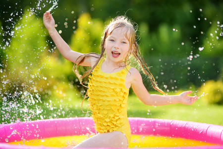 Adorable little girl playing in inflatable baby pool. Happy kid splashing in colorful garden play center on hot summer day. Summer activities for kids. Stockfoto