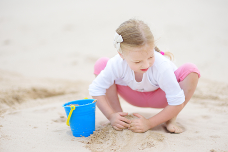 Cute little girl having fun on a sandy beach on warm and sunny summer day. Kid playing by the ocean. Summer activities for children. Banque d'images - 96050985