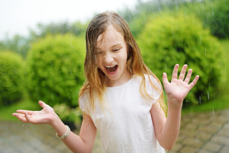 Schattig klein meisje plezier onder warme zomerregen. Kind buiten spelen.
