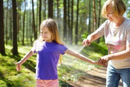 Donna di mezza età che applica repellente per insetti a sua nipote prima della foresta escursione bella giornata estiva. Proteggere i bambini dai morsi di insetti in estate. Svago attivo con i bambini. Archivio Fotografico