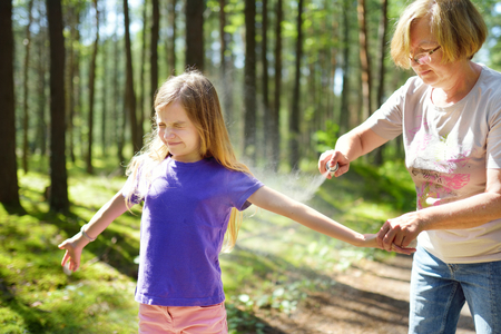 Femme d'âge moyen appliquant un insectifuge à sa petite-fille avant la randonnée en forêt belle journée d'été. Protéger les enfants contre les insectes piqueurs en été. Loisirs actifs avec les enfants. Banque d'images - 96051069