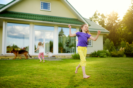 Cute little girl having fun on a grass on the backyard on sunny summer evening. Summer activities for kids.