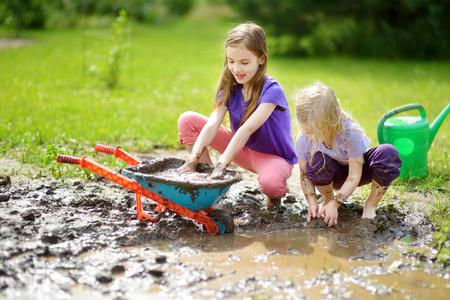 Dos niñas divertidas jugando en un gran charco de barro húmedo en día soleado de verano. Los niños se ensucian mientras cavan en el suelo fangoso. Juegos desordenados al aire libre. Foto de archivo
