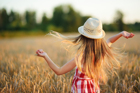 Adorable girl wearing straw hat walking happily in wheat field on warm and sunny summer evening. Cute little child in rye field on sunset.