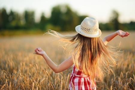 Adorable niña con sombrero de paja caminando felizmente en campo de trigo en la cálida y soleada tarde de verano. Pequeño niño lindo en campo de centeno en la puesta del sol. Foto de archivo