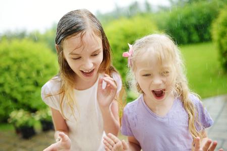 Twee schattige kleine zusjes plezier onder warme zomerregen. Broers en zussen samen buiten spelen.