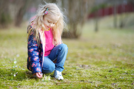 Adorable little girl picking the first flowers of spring on beautiful spring day. Cute child having fun outdoors.