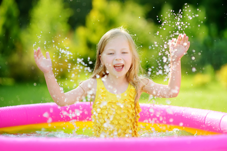 Adorable little girl playing in inflatable baby pool. Happy kid splashing in colorful garden play center on hot summer day. Summer activities for kids. Stock Photo