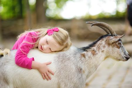 Leuk meisje dat en een geit aait voedt bij kinderboerderij. Kind spelen met een boerderij dier op zonnige zomerdag. Kinderen omgaan met dieren.