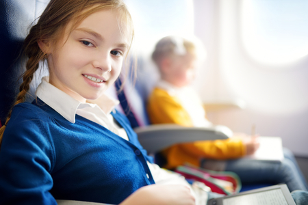 Adorable little girls traveling by an airplane. Child sitting by aircraft window and drawing a picture with colorful pencils. Traveling abroad with kids. Stock Photo