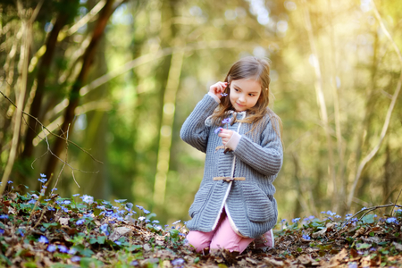 Adorable little girl picking the first flowers of spring in the woods on beautiful sunny spring day. Cute child having fun outdoors. Stock Photo