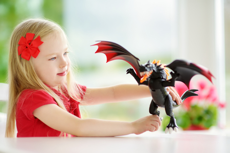 Cute little girl playing with toy dragon at home. Child having fun with big plastic toy. Fantasy and imagination concept. Stock Photo