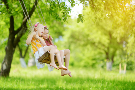 Two cute little sisters having fun on a swing together in beautiful summer garden on warm and sunny day outdoors. Active summer leisure for kids.