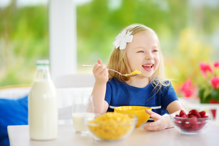 Cute little girl enjoying her breakfast at home. Pretty child eating corn flakes and raspberries and drinking milk before school. Healthy nutrition for small children.