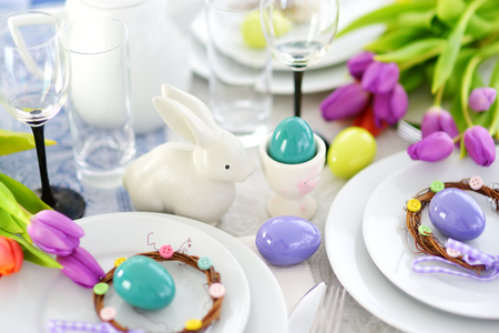 Beautiful table setting with crockery and flowers for Easter celebration. Glassware and cutlery for catered event dinner.