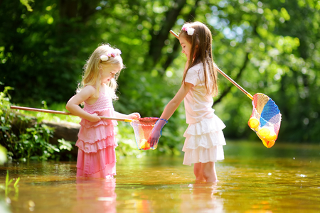Two cute little sisters playing in a river catching rubber ducks with their scoop-nets on warm and sunny summer day. Active summer leisure for kids.