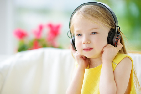 Cute little girl wearing huge wireless headphones. Pretty child listening to the music. Schoolgirl having fun listening to kids songs at home. Home, technology and music concept.