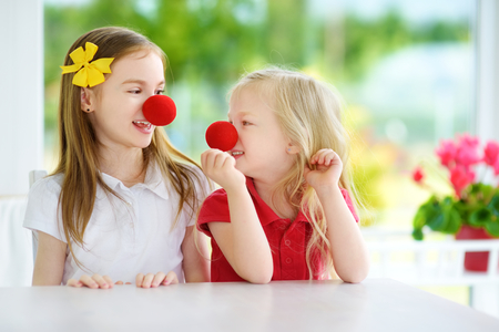 Happy little sisters wearing red clown noses having fun together on sunny summer day at home. Two kids playing together.