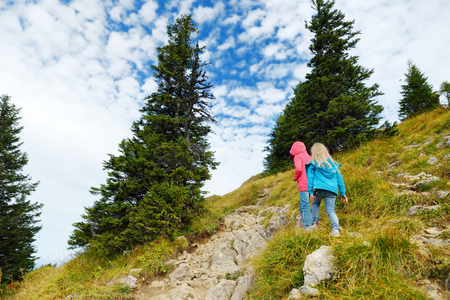 Two sisters enjoying picturesque views from the Tegelberg mountain, a part of Ammergau Alps, located nead Fussen town, Bavaria, Germany. Foto de archivo
