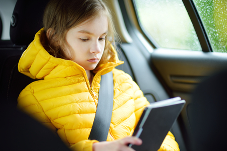 Adorable girl sitting in a car and reading her ebook on rainy autumn day. Child entertaining herserf on a road trip. Traveling by car with kids.