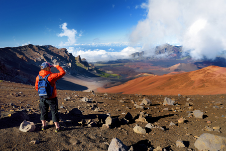 Tourist hiking in Haleakala volcano crater on the Sliding Sands trail. Beautiful view of the crater floor and the cinder cones below. Maui, Hawaii, USA. Stock Photo