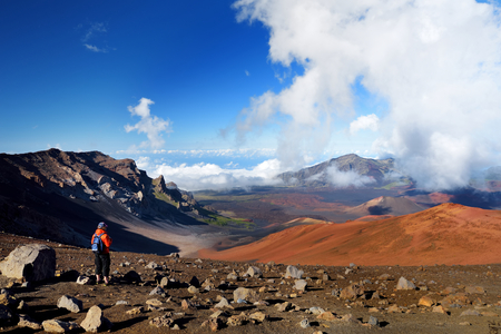 Tourist hiking in Haleakala volcano crater on the Sliding Sands trail. Beautiful view of the crater floor and the cinder cones below. Maui, Hawaii, USA. 스톡 콘텐츠