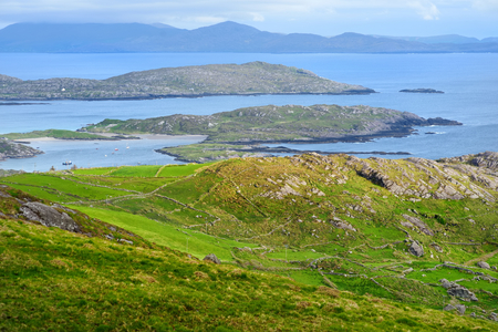 Beautiful view of Derrynane Bay on the Iveragh Peninsula. Famous picturesque Ring of Kerry route of Ireland. Rocky islands set in a blue sea form a natural harbour for little boats. Stock Photo
