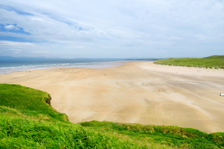 Spectacular Tullan Strand, one of Donegal's renowned surf beaches, framed by a scenic back drop provided by the Sligo-Leitrim Mountains. Wide flat sandy beach in County Donegal, Ireland. Imagens