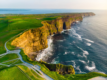 World famous Cliffs of Moher, one of the most popular tourist destinations in Ireland. Aerial view of widely known tourist attraction on Wild Atlantic Way in County Clare. Фото со стока
