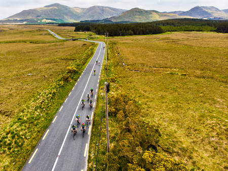 Professional cyclists competing in Connemara region in Ireland. Scenic Irish countryside landscape with magnificent mountains on the horizon, County Galway, Ireland.