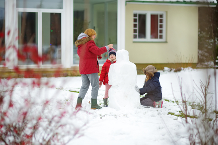 Cute little girls and their grandma building a snowman in the backyard. Cute children playing in a snow. Winter activities for kids. Banco de Imagens