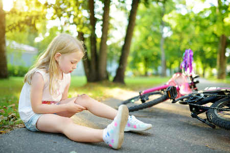 Cute little girl sitting on the ground after falling off her bike at summer park. Child getting hurt while riding a bicycle. Active family leisure with kids. Stok Fotoğraf