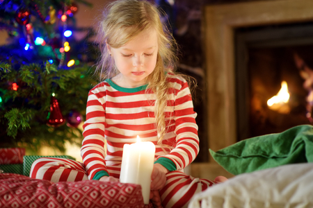 Happy little girl wearing Christmas pajamas playing by a fireplace in a cozy dark living room on Christmas eve. Celebrating Xmas at home.