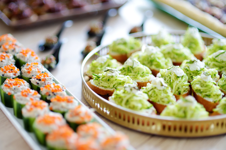 Delicious zucchini and mint mini bruschettas served on a party or wedding reception. Plates with assorted fancy finger food snacks on an event party or dinner.