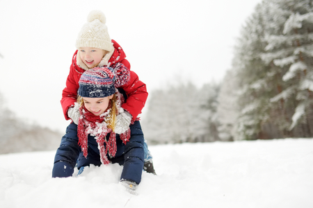 Two adorable little girls having fun together in beautiful winter park. Beautiful sisters playing in a snow. Winter activities for kids. Zdjęcie Seryjne