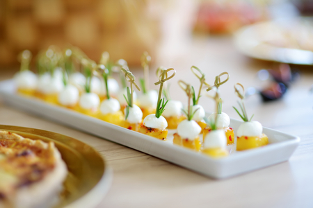 Delicious baked pineapple and mozzarella mini snacks served on a party or wedding reception. Plates with assorted fancy finger food snacks on an event party or dinner. Imagens