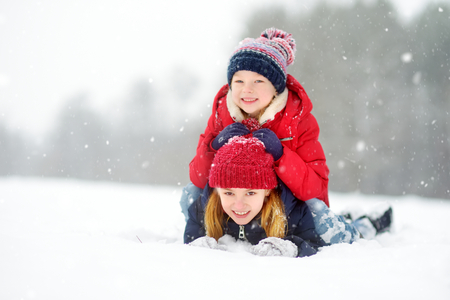 Two adorable little girls having fun together in beautiful winter park. Beautiful sisters playing in a snow. Winter activities for kids. Banco de Imagens