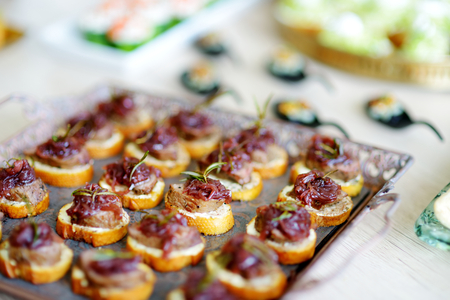 Delicious pate snacks with beet topping served on a party or wedding reception. Plates with assorted fancy finger food snacks on an event party or dinner.