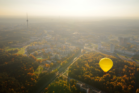 Yellow hot air balloon flying over Vilnius city on sunny autumn evening. Vilnius is one of the few European capital cities, where hot air balloons are allowed to fly. Фото со стока