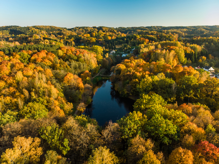 Birds eye view of autumn forest and a small lake. Aerial colorful forest scene in autumn with orange and yellow foliage. Fall scenery near Vilnius, Lithuania.